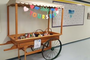 a wooden cart with wheels filled with food with a sign that says help yourself