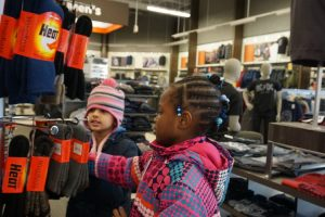 two younger kids wearing winter coats looking at winter gloves on a rack