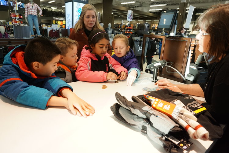 several young students looking at a pair of gloves held by an employee of the store they are in