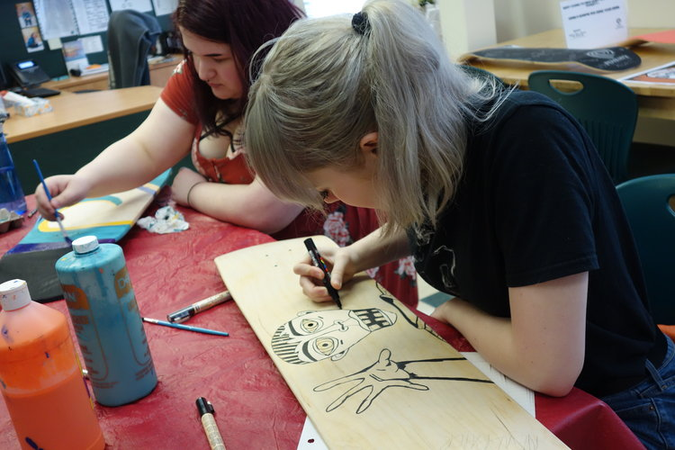 two female students drawing each drawing on a skateboard