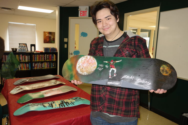 a teenage student holding a painted skateboard