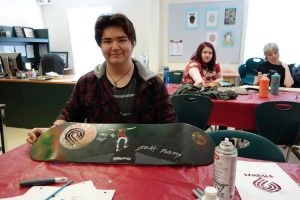 a teenage kid wearing a sweater holding a skateboard that he painted