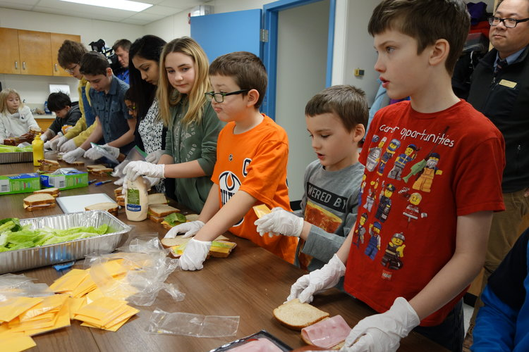 female and male students making sandwiches with cheese while wearing gloves