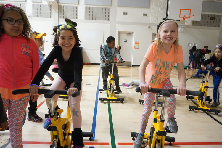 some smiling kids on spin bikes inside a gymnasium