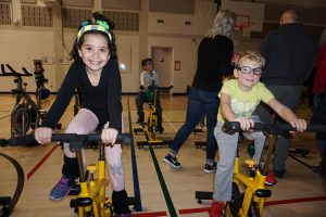 a female and male student smiling on spin bikes in a gym with people in the background