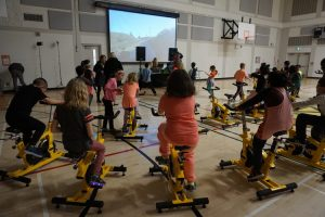 a group of students on spin bikes in a gymnasium in front of a projection screen