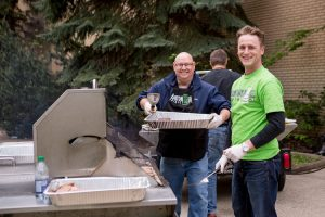a male holding a tray of food and a male in a bright green shirt holding a bbq flipper