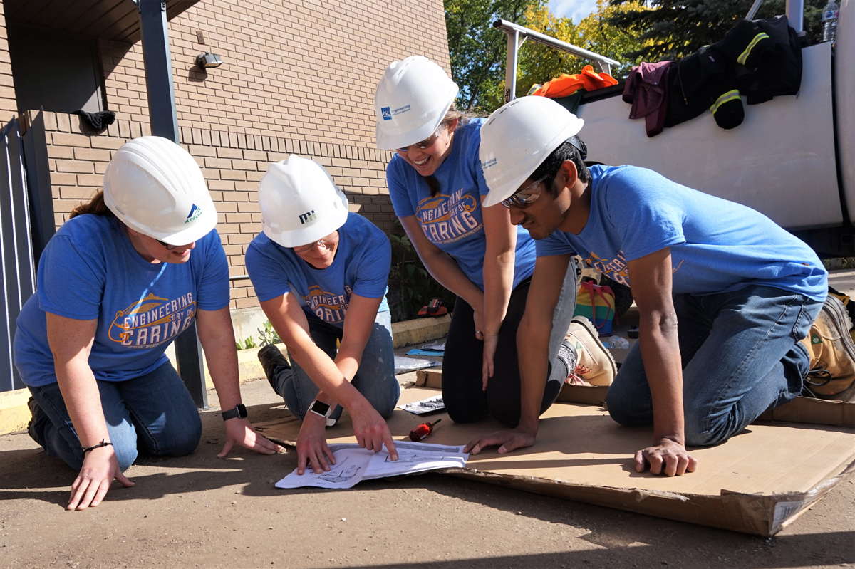 engineers look over plans during engineering day of caring