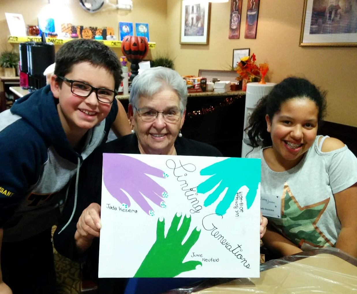 two children and a senior hold up a linking generations sign