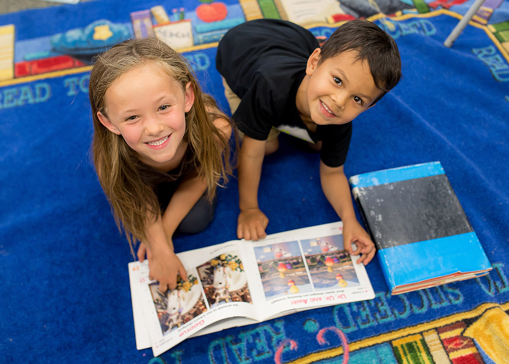 two preschool children reading a book smile at the camera
